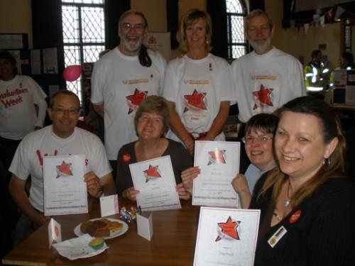 CVS Volunteers with their Volunteers Week Certificates. The Volunteer Centre tteam are standing behind them